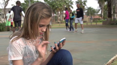 Teenager sitting in park texting on cell phone with other children playing Stock Footage