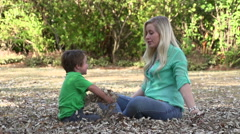 Slow motion of mother and child sitting on ground and throwing leaves into the Stock Footage