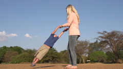 Slow motion and low angle view of mother playing and swinging child around in a Stock Footage