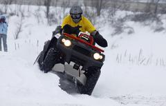 The quad bike's driver rides over snow track Stock Photos