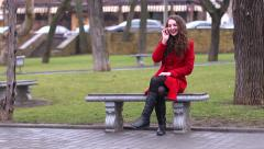 Girl in a red coat on a park bench - funy talking on the phone laughing Stock Footage
