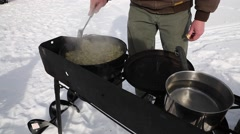 Cooking breakfast in a dutch oven while ice fishing - stock footage