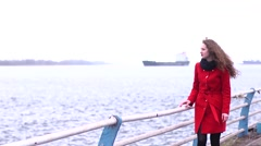 Bright beautiful girl in red coat relaxing on the promenade near the water Stock Footage