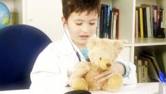 Beautiful doctor child visiting teddy bear in medical office - stock footage