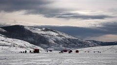 Ice fishing on a reservoir in the snowy mountains Stock Footage