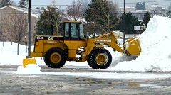 Front Loader moves snow drifts, parking lot Stock Footage