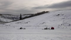 Kids sled down hill while families ice fish panning shot Stock Footage