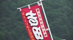 Red Japanese Banner Infront Of Green Forest Stock Footage