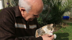 Senior man playing a cat in the garden 2 Stock Footage