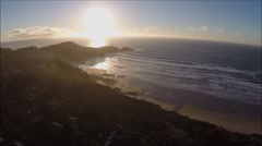 Aerial small cove beach waves and lighthouse approaching sunset.mp4 Stock Footage
