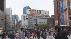 Crowded people cross street downtown Tokyo tall building busy traffic road car Stock Footage