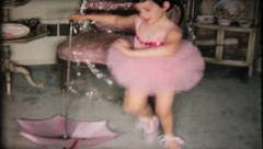 1677 - little ballerina dances around umbrella at home - vintage film home movie Stock Footage