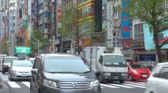 Heavy street traffic car pass Tokyo downtown neon sing shop transport commuting  Stock Footage