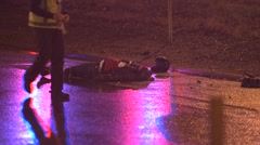 Fatal Motorcycle crash  body laying in the street .person walks by Stock Footage