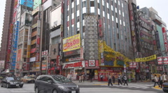 Heavy traffic street commercial district Tokyo downtown people travel car pass  Stock Footage
