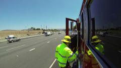 First responders firefighter getting into fire truck side freeway yellow jacket Stock Footage