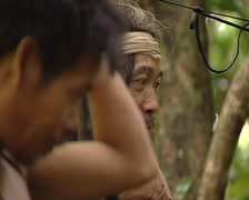 Mix of cultures. Caucasian man with punan tribe assembling a tent Stock Footage