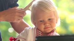 Mother combing blonde small smiling girl closeup Stock Footage