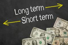 Text on blackboard with money - Long term and short term - stock illustration