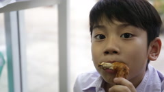 Asian child eating chicken wing Stock Footage