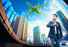 young business man and belonging luggage standing against building urban scen - stock photo
