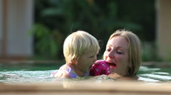 Small blonde child swim with mother Stock Footage