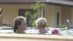small blonde child swim with mother - stock footage