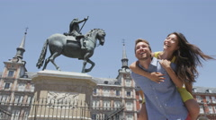 Couple laughing having fun piggybacking happy  - Plaza Mayor, Madrid, Spain Stock Footage