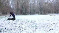 Camera pans down to a little girl playing in the snow in a woods clearing Stock Footage