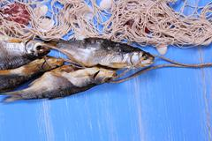 Dried rudd fish and fishing net on blue background - stock photo