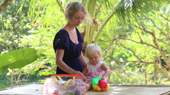 Child play with toys sitting beside her mother Stock Footage