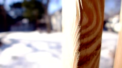Quick side slide of a wood deck railing with snow covered ground in background. Stock Footage