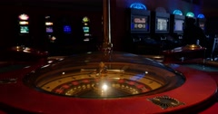 A 4k wide shot of a casino roulette in the foreground and some slot machines Stock Footage
