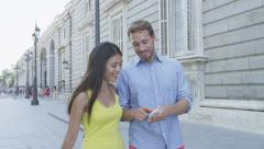 Couple using mobile smart phone outdoors in city looking at smartphone screen Stock Footage