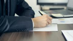 Businessman writing on the sheet of paper Stock Footage