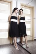 Nice lady posing in black dress behind mirrow Stock Photos