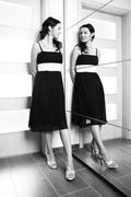 Beauty lady posing in black dress behind mirrow Stock Photos