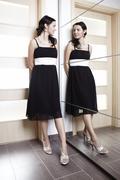 Nice woman posing in black dress behind mirrow Stock Photos