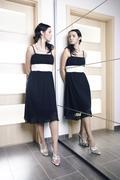 Beauty woman posing in black dress behind mirrow Stock Photos