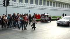 Tour groups cross road outside grand palace Bangkok Stock Footage