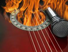 Guitar and microphone burning in the fire Stock Photos