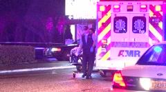 Patient being taken to awaiting ambulance . night shot lots of flashing lights - stock footage