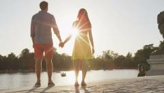 Stock Video Footage of Romantic couple holding hands at sunset in park - romantic lovers