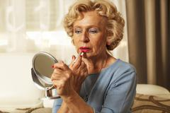 Elderly woman applied lipstick and looked in the mirror Stock Photos