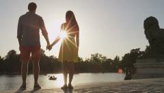 Romantic couple holding hands at sunset in Madrid in el Retiro, Spain Stock Footage