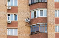 Mounting the air conditioner on the wall of an apartment house - stock photo
