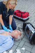 Paramedic examining unconscious patient - stock photo