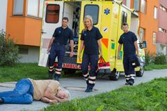 Paramedics arriving to unconscious man - stock photo