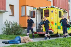 Emergency team running to unconscious man - stock photo