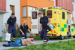 Paramedical team arriving to unconscious elderly man Stock Photos